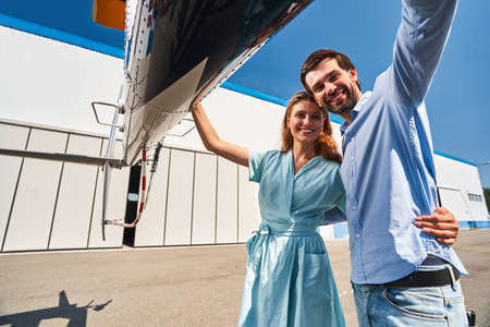 Romantic couple standing by chopper parked on helipad