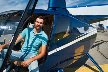Happy male pilot posing for camera before helicopter flight Standard-Bild