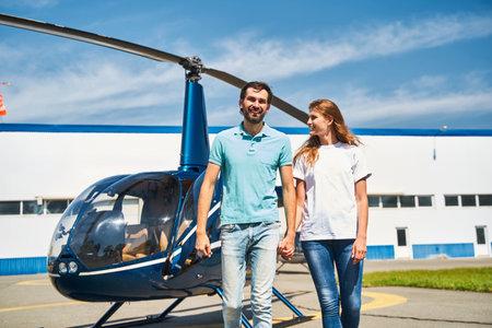 Joyous romantic couple walking across the helipad