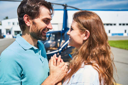 Happy romantic tourist couple standing by helicopter Standard-Bild