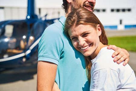 Joyous romantic lady hugging man at heliport