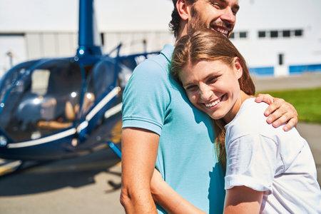 Woman in love embracing pleased guy on helipad