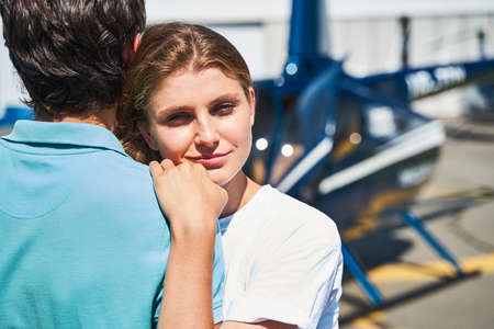 Loving Caucasian lady hugging man by helicopter