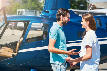 Romantic man talking to young woman by helicopter Standard-Bild
