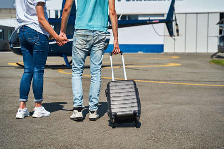 Caucasian tourist couple with baggage on helipad