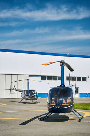 Empty choppers standing on landing pad on clear day