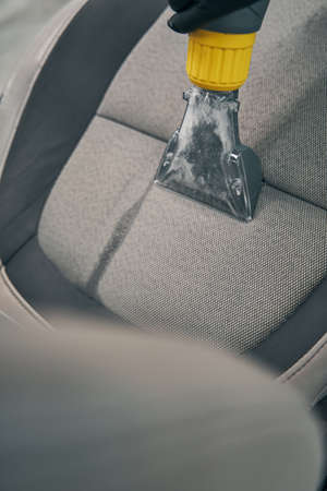 Specialist vacuums removed front seat at car service closeup Standard-Bild