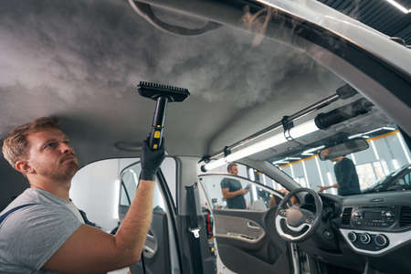 Dry cleaning salon car. Worker uses professional steam cleaner