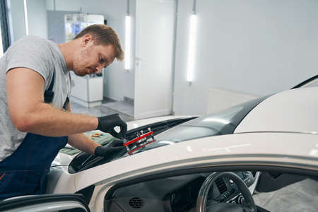Closeup of man working with vacuum filler repair cracks in windshield