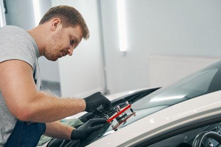 Mechanic man is applying glue on cracked front window of car closeup