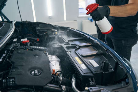 Cleaning car engine with foam spray by serviceman. Dry auto washing