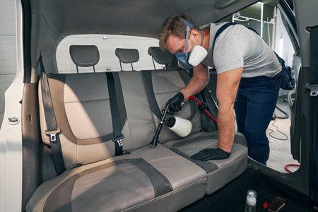 Serviceman in respirator chemically wash car interior of rear seats
