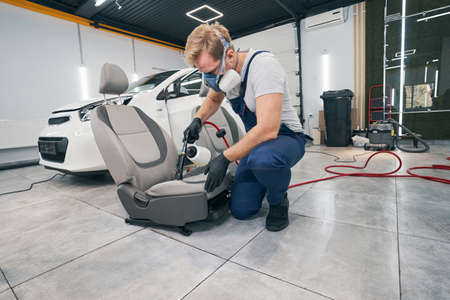 Car service technician performs chemical cleaning of textile seats
