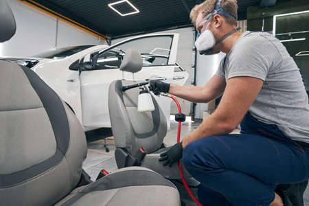 Specialist man performs chemical cleaning of car interior seats
