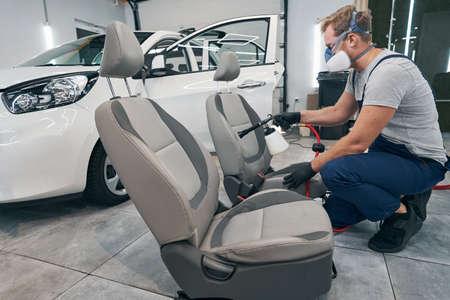 Car seats chemical cleaning with gun at auto service closeup Standard-Bild