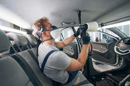 Car interior headlining fabric chemical cleaning with professional gun Standard-Bild