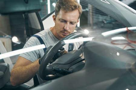 Man auto shop worker washes steering wheel with foam closeup portrait