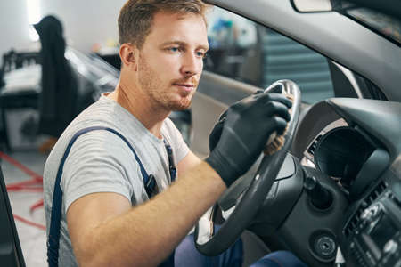 Service employee cleans wheel, dashboard with disinfectants side view
