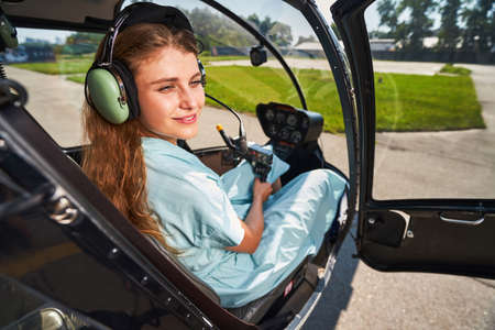 Happy airwoman daydreaming in cockpit of private chopper