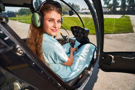 Joyous airwoman sitting in helicopter cabin before flight
