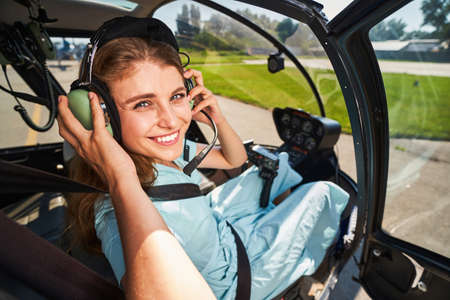 Smiling female pilot putting on headphones before flight Standard-Bild