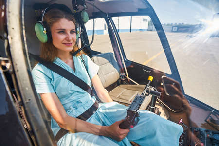 Pleased tranquil female pilot getting ready to fly chopper