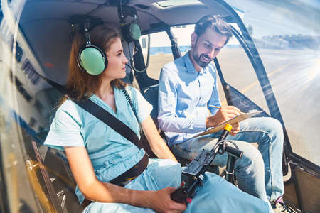 Young woman taking flying lesson from experienced airman