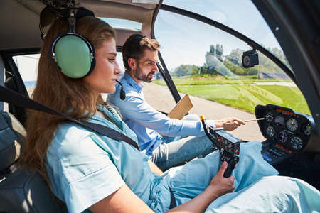 Serious concentrated young woman undergoing flight instruction
