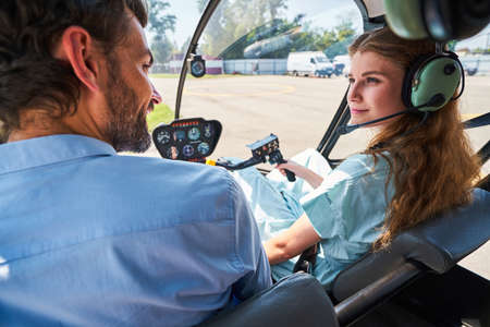 Attentive lady listening to helicopter instructor during pre-flight instruction Standard-Bild
