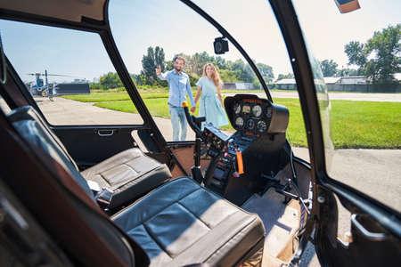 Joyous romantic couple looking at chopper at heliport