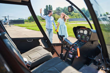 Romantic couple standing before helicopter on helipad