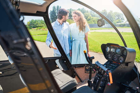 Guy demonstrating his private aircraft to delighted lady