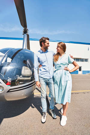Joyous loving couple standing by helicopter at heliport