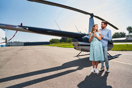 Romantic young couple standing by private helicopter
