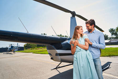 Happy young couple standing by private helicopter