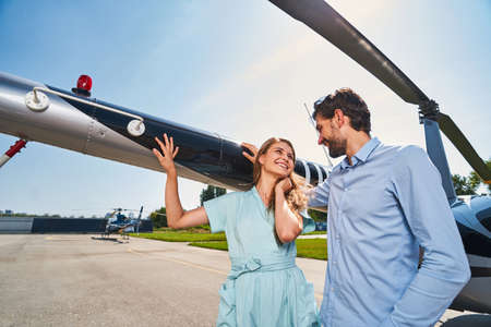 Young loving couple standing by chopper parked on helipad