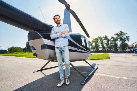 Cheerful man standing by chopper at heliport Standard-Bild