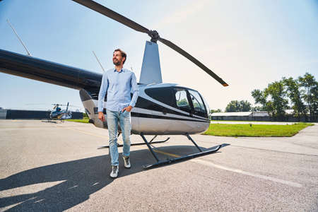 Joyous young man by helicopter at heliport