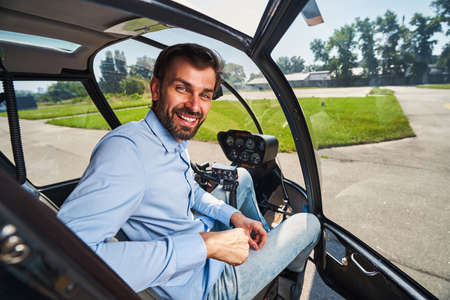Joyful airman posing for camera in helicopter cabin