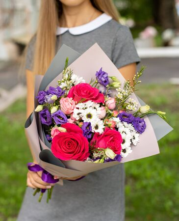Girl in grey dress holding a beautiful pink and purple, fresh blossoming flowers bouquet. Outside, no face, close up.