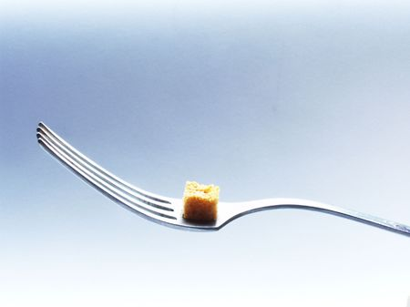dinnertime: Fork with a rusk like a symbol of extreme diet. on the other hand, it is symbol of balance in diet.