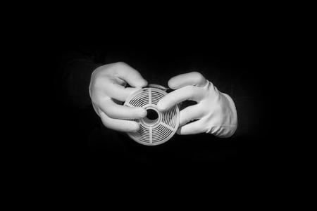 darkroom: laboratory, hands in white gloves hold a black and white film, darkroom, film development