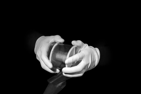 white gloves: laboratory, hands in white gloves hold a black and white film, darkroom, film development