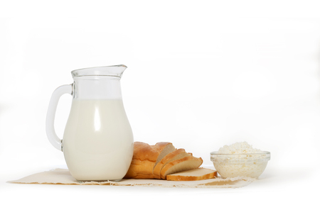 Glass jug with milk, bowl of cottage cheese and white bread on w
