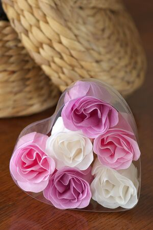 dressing table: Wicker casket and bathroom soap as roses on wood dressing table. Selective focus at roses.