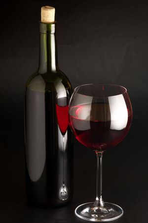 Glass of red wine and bottle on black background. Stock Photo - 4070181