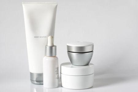 Set of cosmetic products in white and grey containers on light background. photo