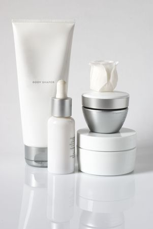 cleanser: Set of cosmetic products in white and grey containers on light background.