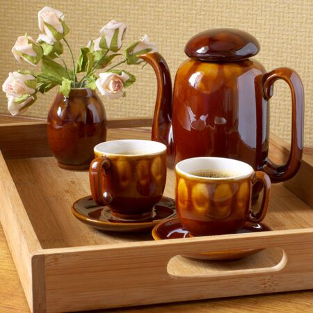 Coffee-pot, two cup with cooffee and rose bouquet on wooden tray. photo