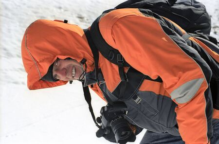 Smailing man in orange sports jacket with photocamera on snow. photo